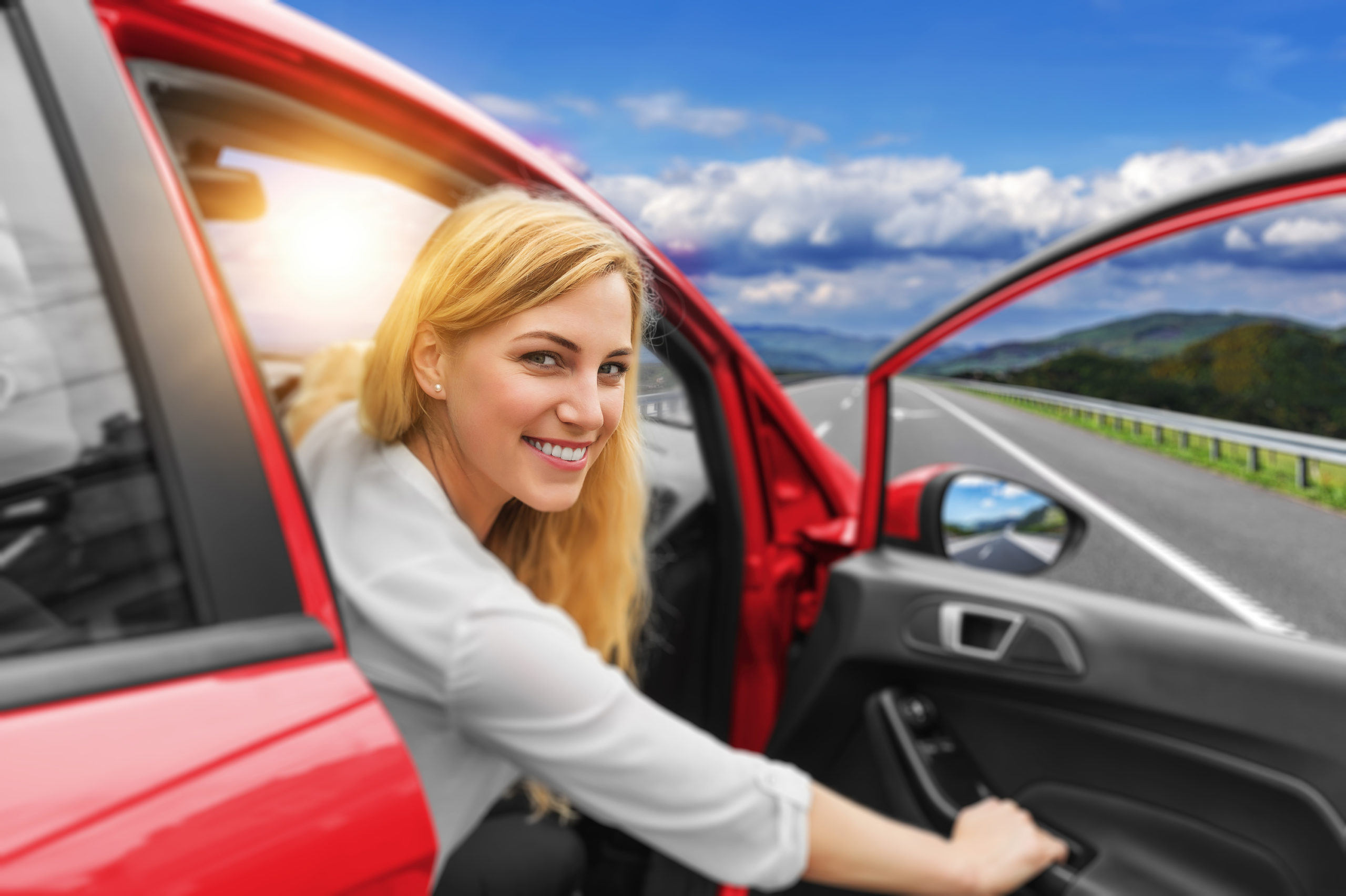 Beautiful blonde girl driving a car on the highway. The woman opens the car door. Invitation to travel. Car rental or vacation.